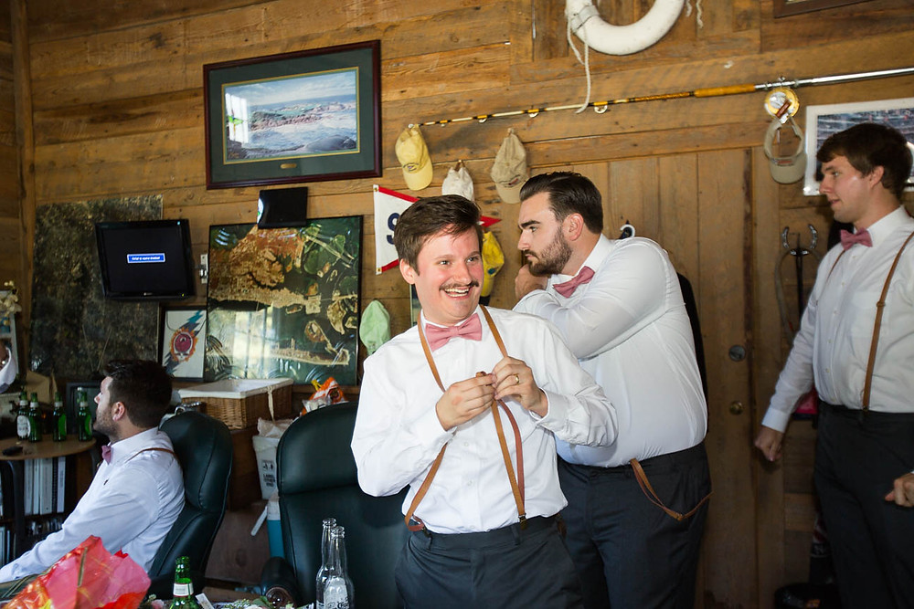 groomsmen laugh as they put on suspenders