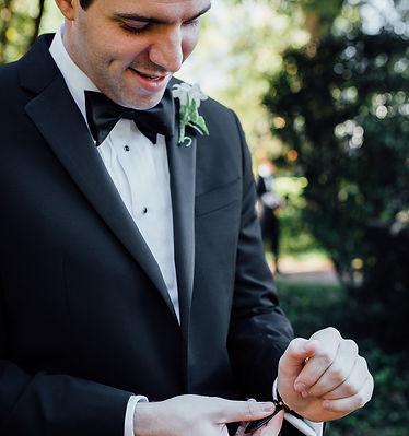 Image of groomsman helping groom put on his jacket before his Memphis, TN wedding ceremony