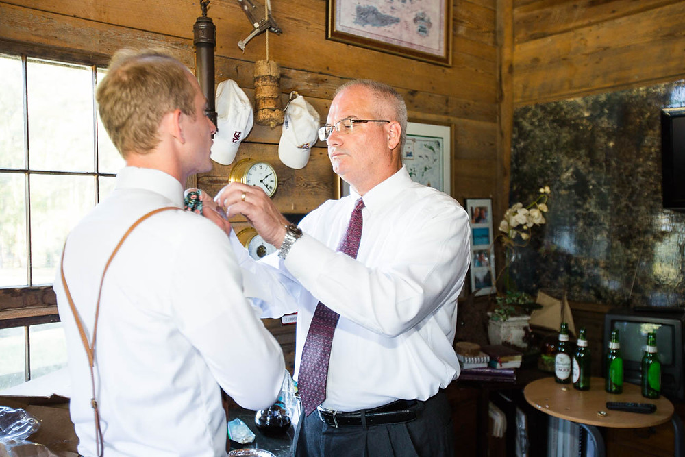 father of groom helps him straighten his bowtie