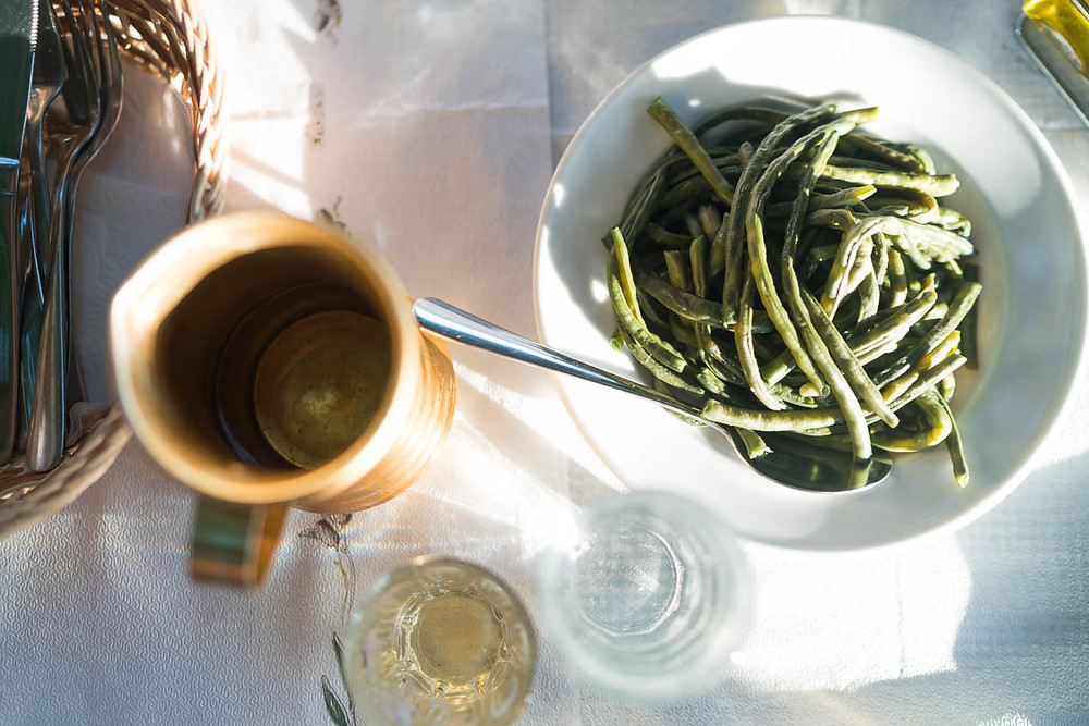 green beans and local white wine at farm to table restaurant in Greece