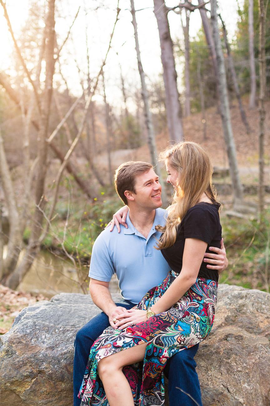 bride sits on groom's lap in Asheville park, Asheville engagement session