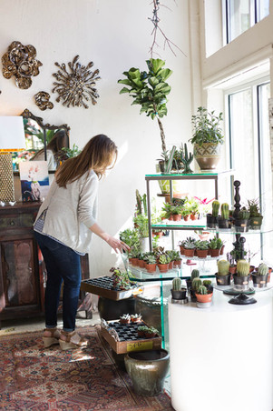 store owner waters plants in her shop