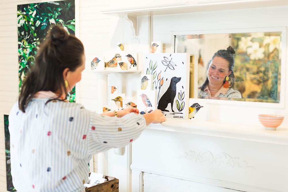 image of a decorator arranging art on a mantle