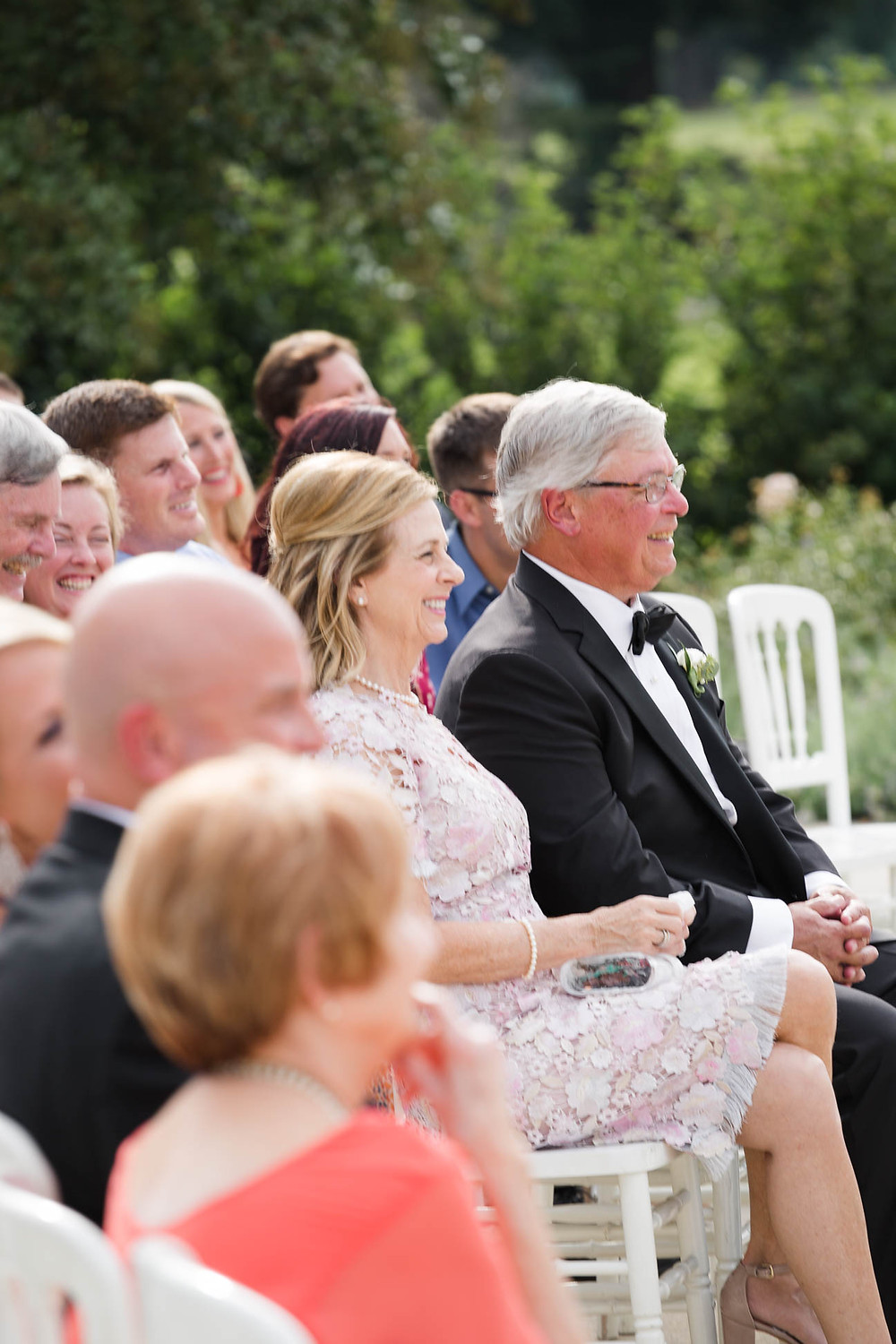 brides parents happily watch their daughter get married