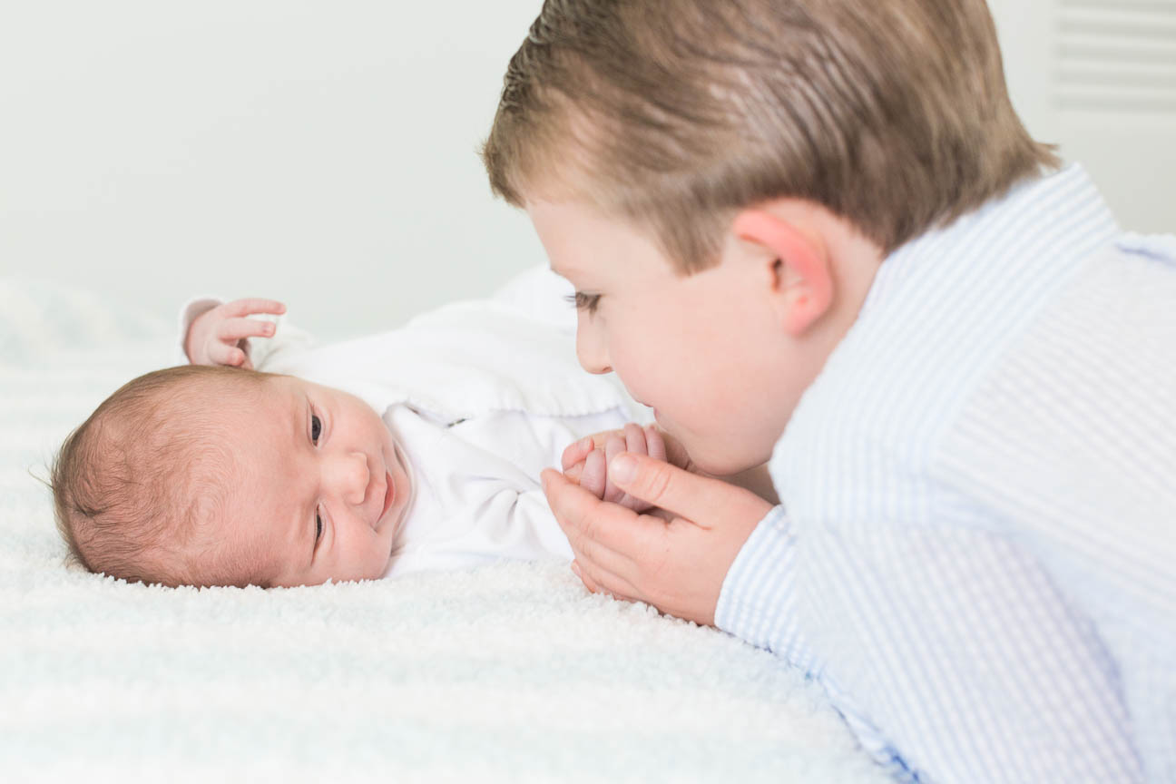 brother holds new baby's hand