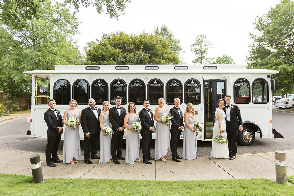 bridesmaids and groomsmen with the newlyweds in front of a white trolley
