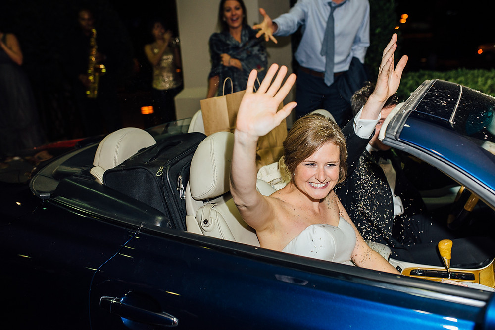 image of newlyweds leaving their wedding in a convertible