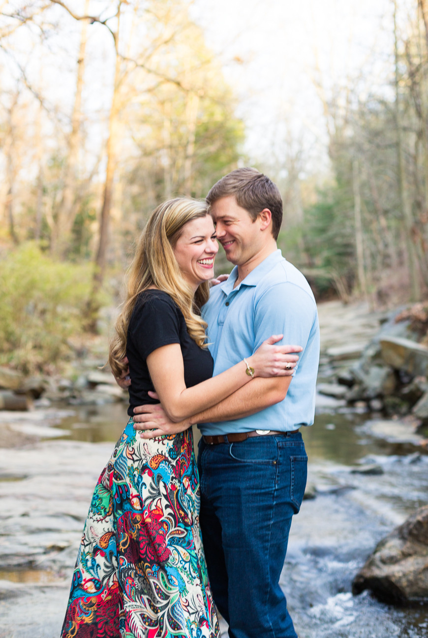 couple stands in creek smiling, Asheville engagement session