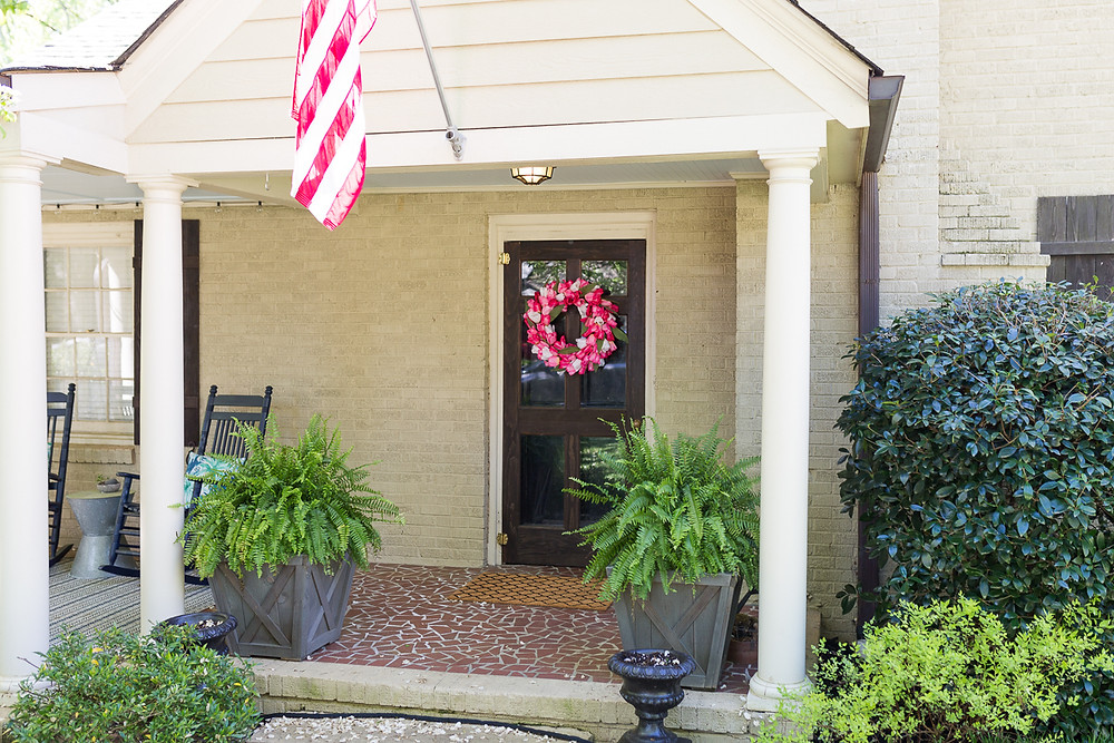 image of a homemade pink tulip wreath on the front door of a house