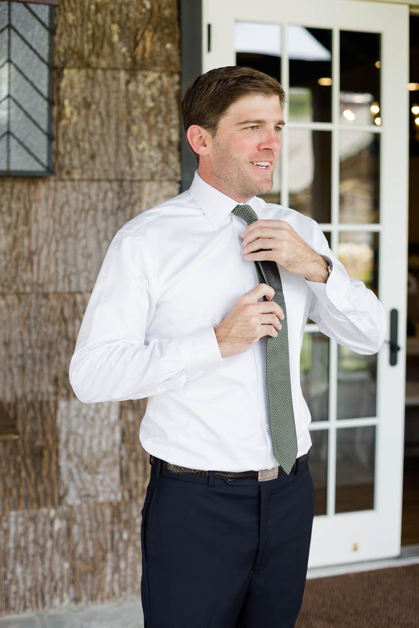 groom ties his tie