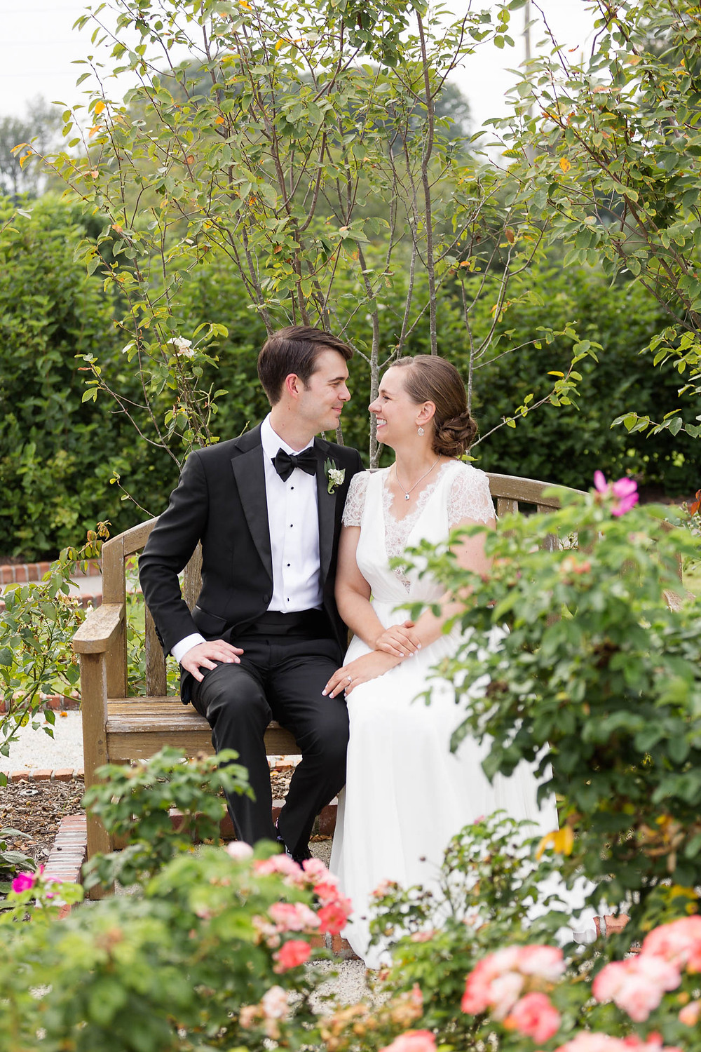 bride and groom sit among the roses in a garden