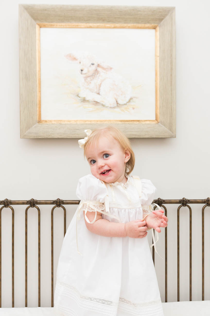 girl stands in crib smiling
