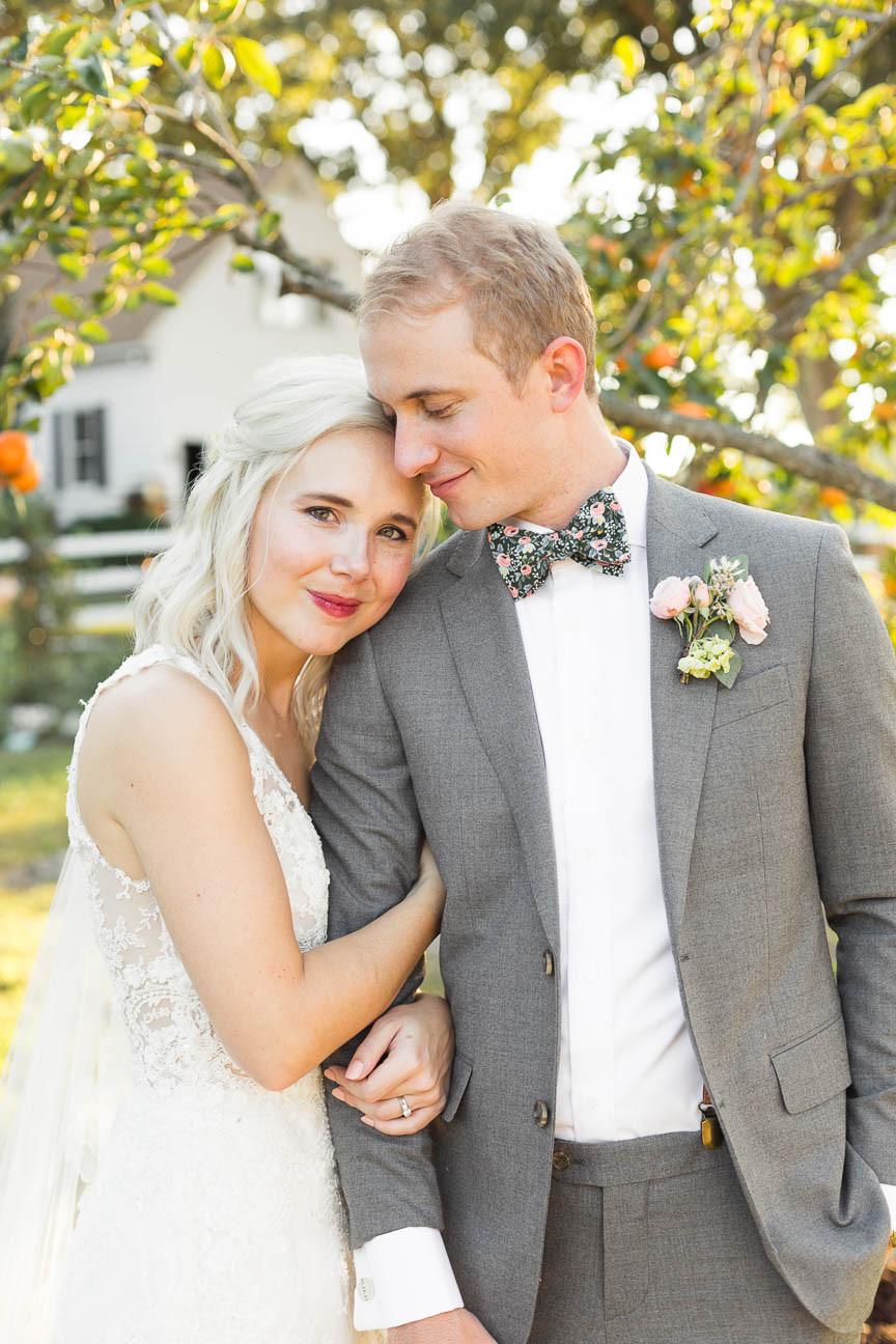groom looks lovingly down at his bride