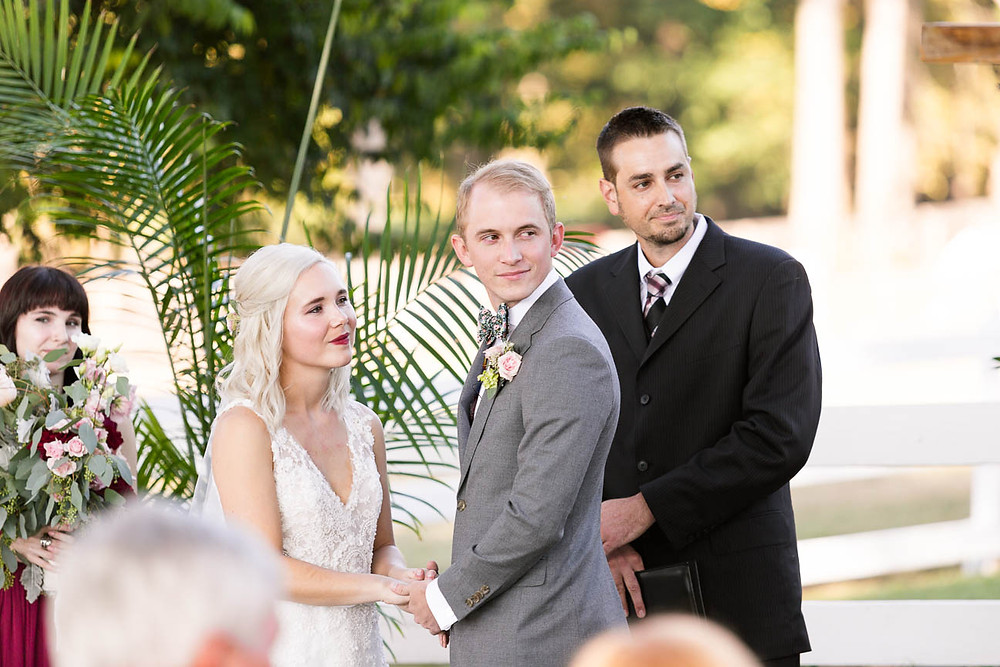 bride and groom listen to friend reading scripture at their ceremony