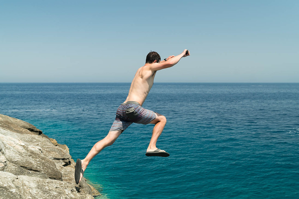 traveler jumps off of a cliff into the Agean Sea on the island of Paros