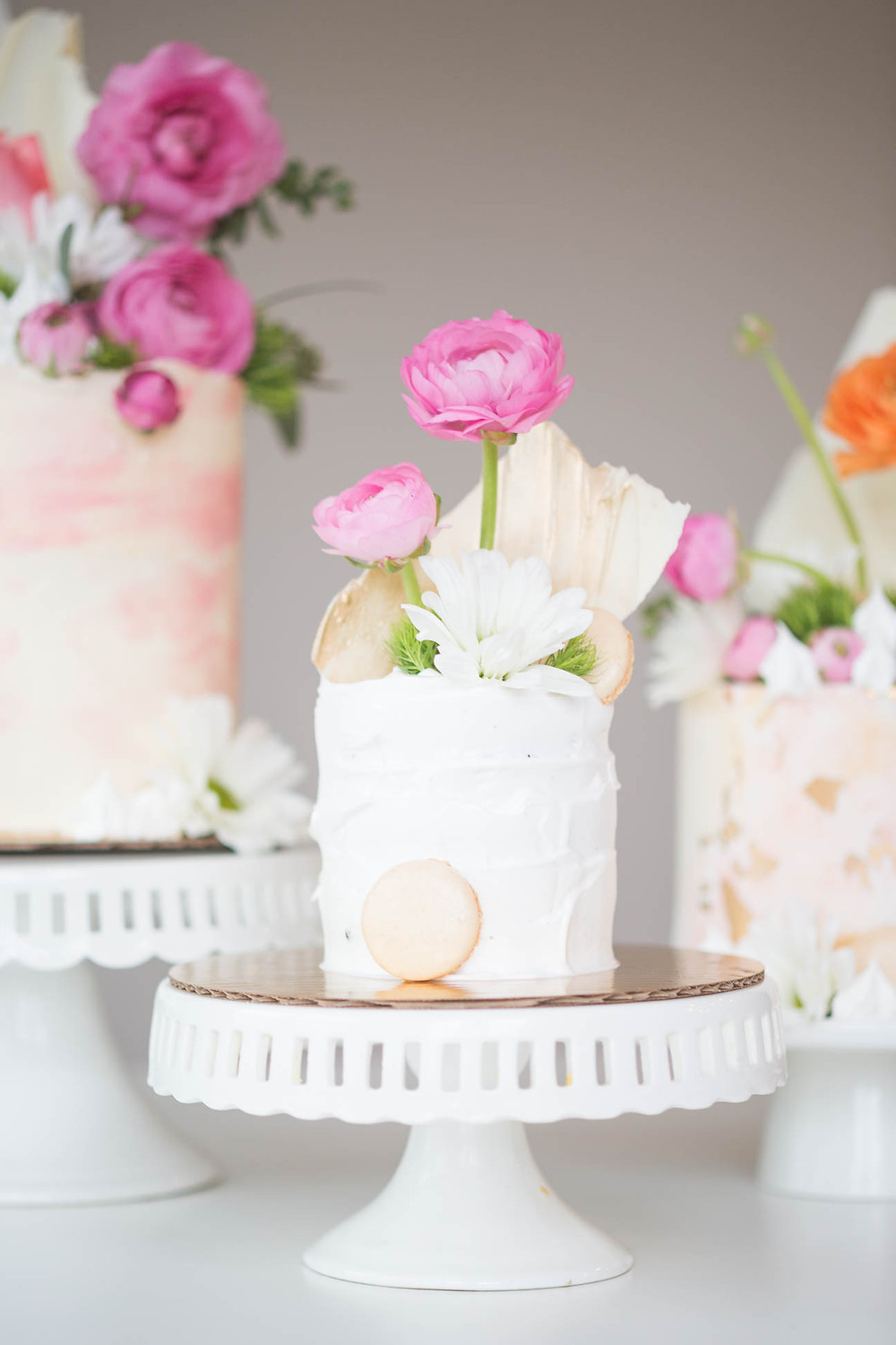 small wedding cake trip decorated with macaroons, florals, and white and pink icing