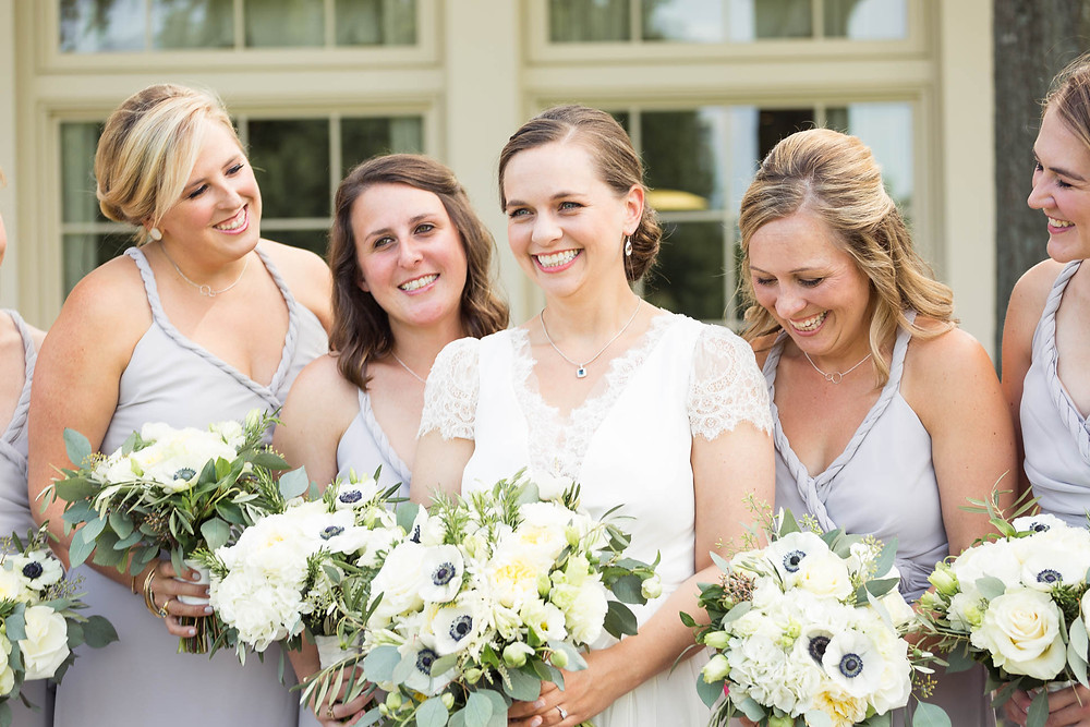 bride laughs with her bridesmaids