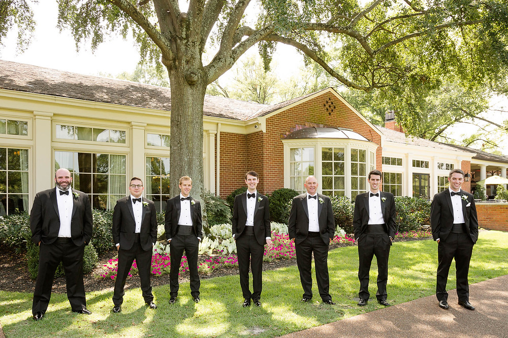 portrait of groom and groomsmen standing outside country club