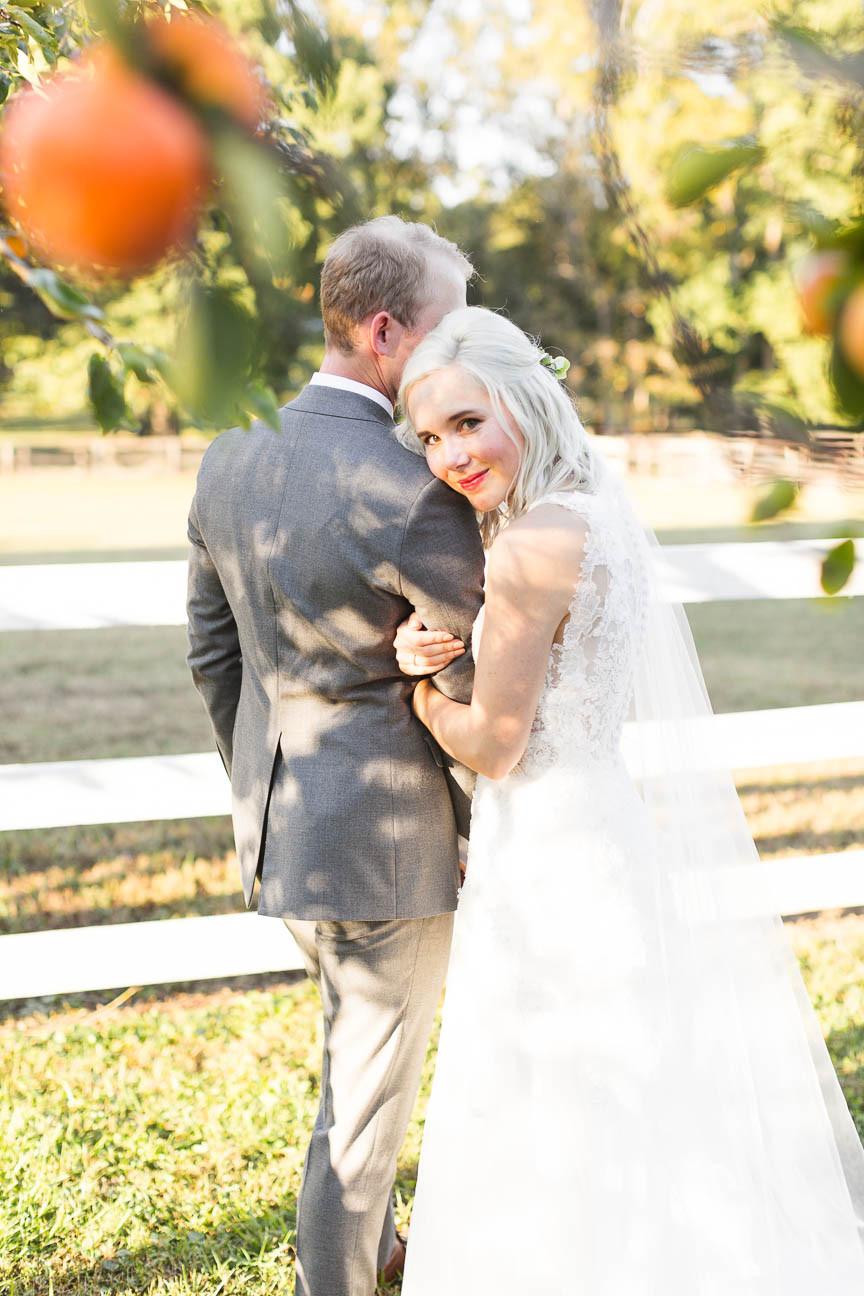 bride looking through persimmon tree
