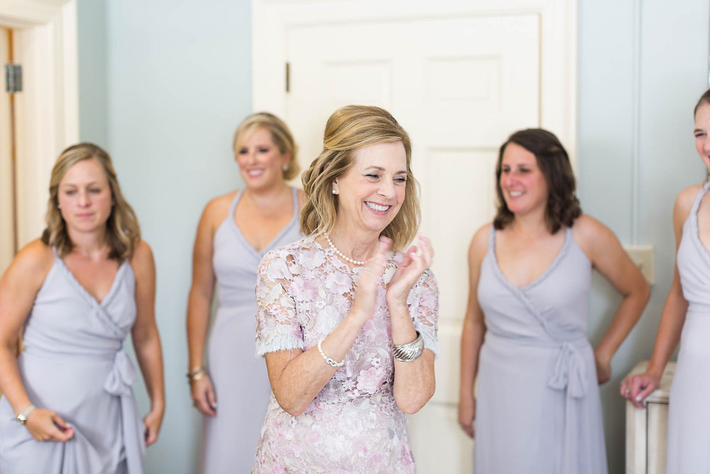 mother of the bride smiles as she watches her daughter putting on her wedding dress