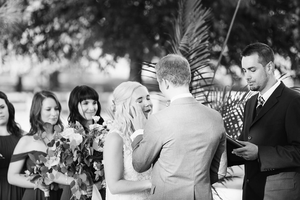 groom wipes a tear from the bride's eye during their ceremony