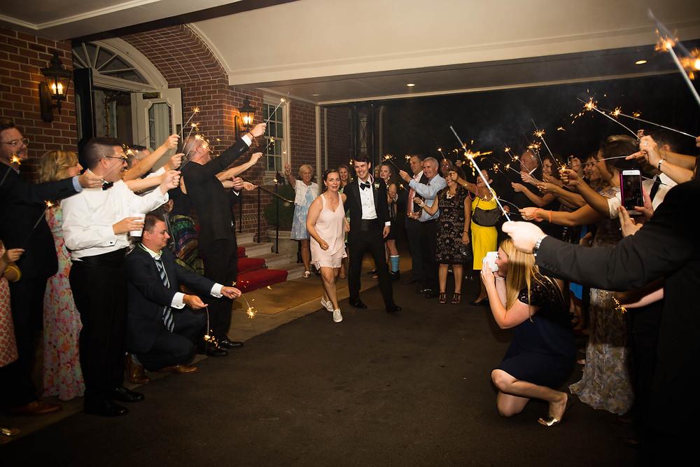 bride and groom run through sparkler tunnel