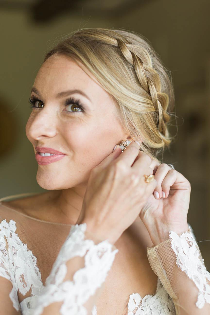 bride puts on earrings before her NC wedding