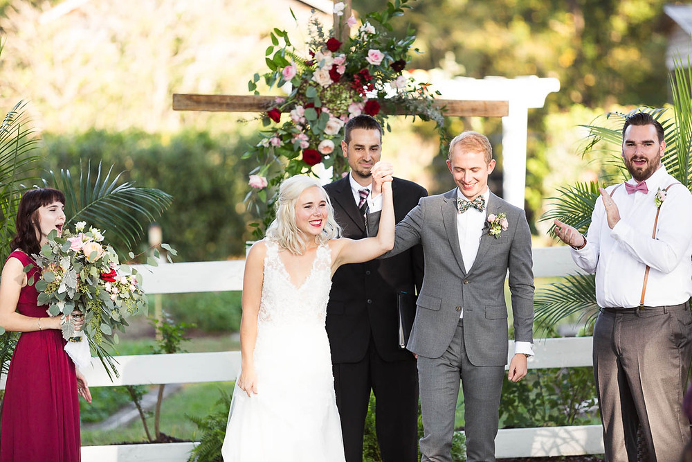 newlyweds celebrate as they walk down the aisle together