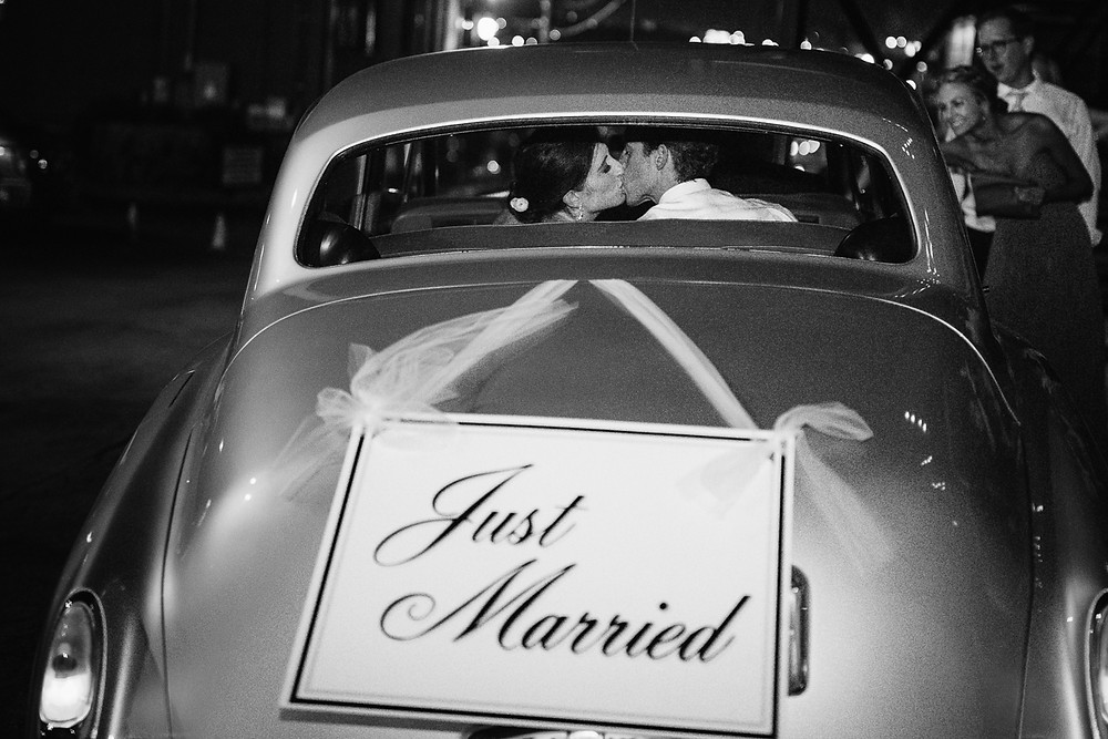 image of newly married couple kissing through the window of vintage car
