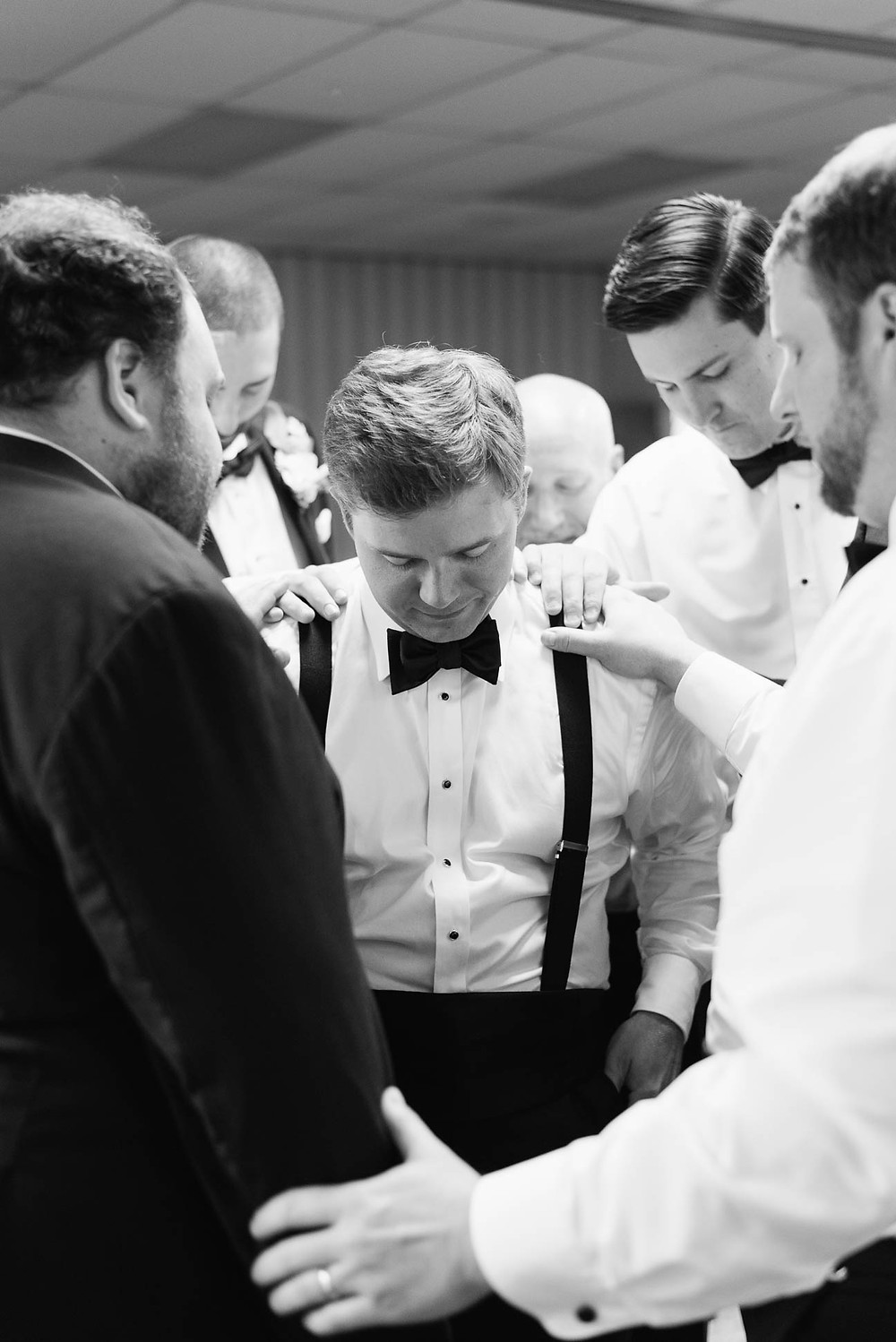 groomsmen pray over the groom before his ceremony
