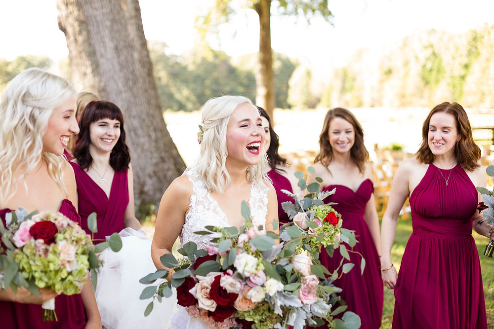 bride and bridesmaids laugh as they walk to ceremony