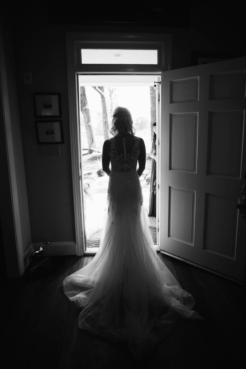 black and white portrait of back of bride standing in her dress in the doorway