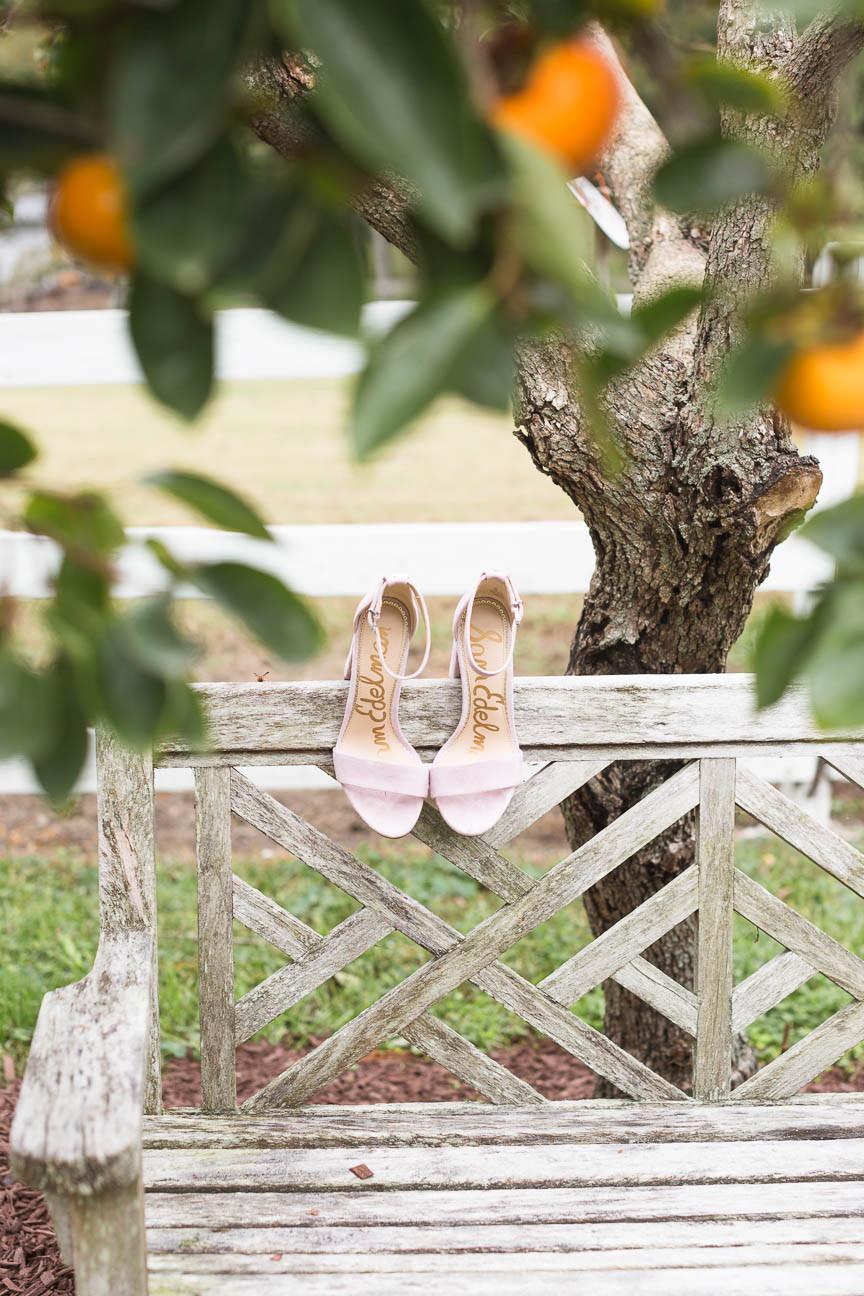 bride's pink Sam Edleman shoes under persimmon tree, detail shot