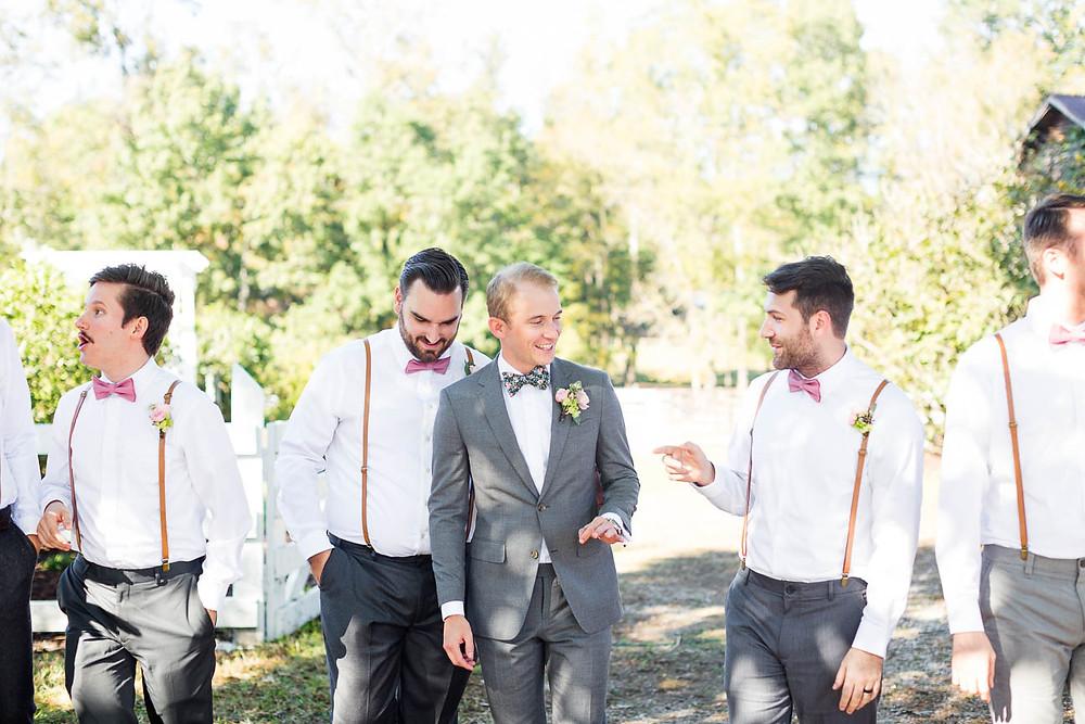 groom laughs with groomsmen before his wedding