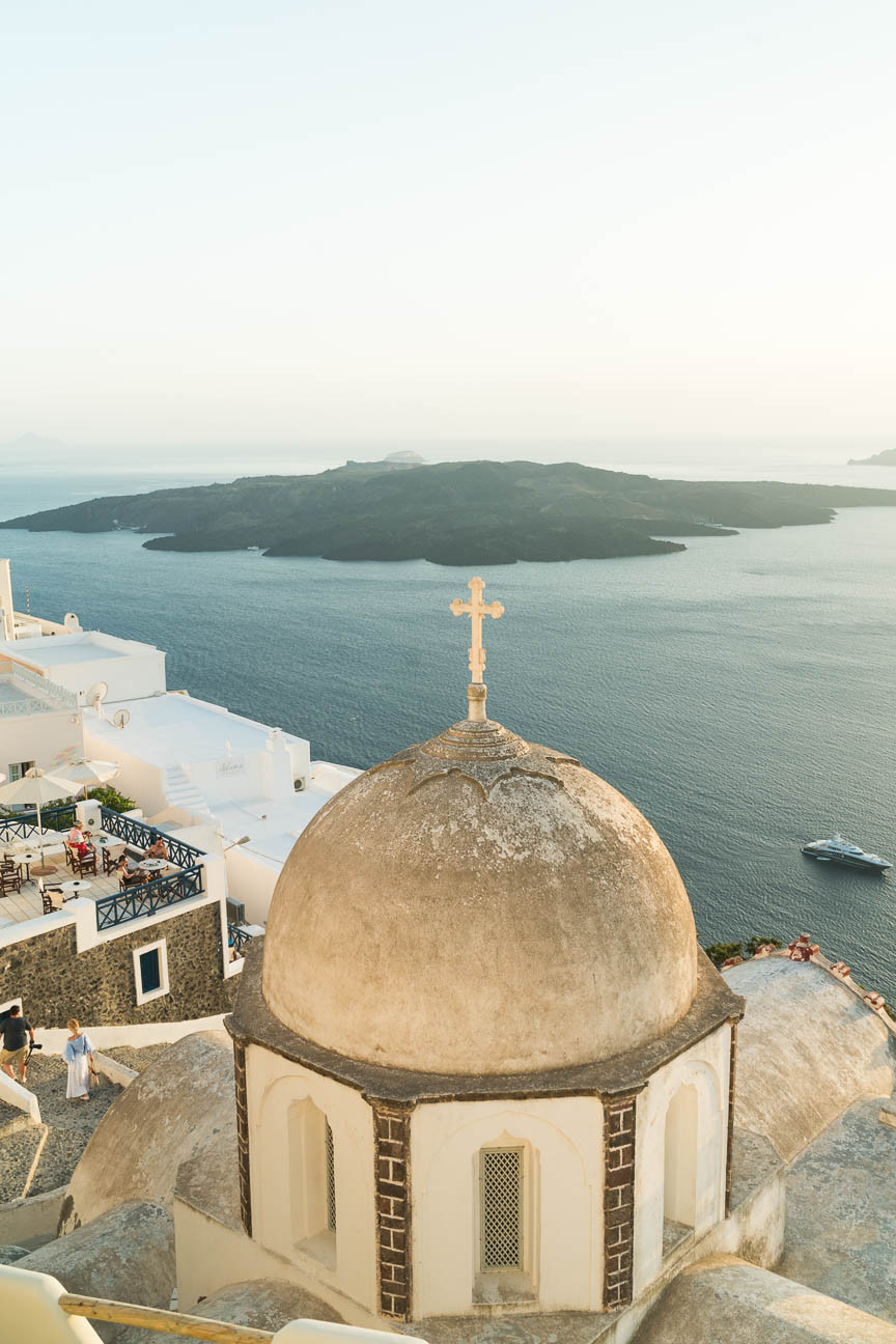 View of a cross dome overlooking the Caldera and Agean Sea in Greece