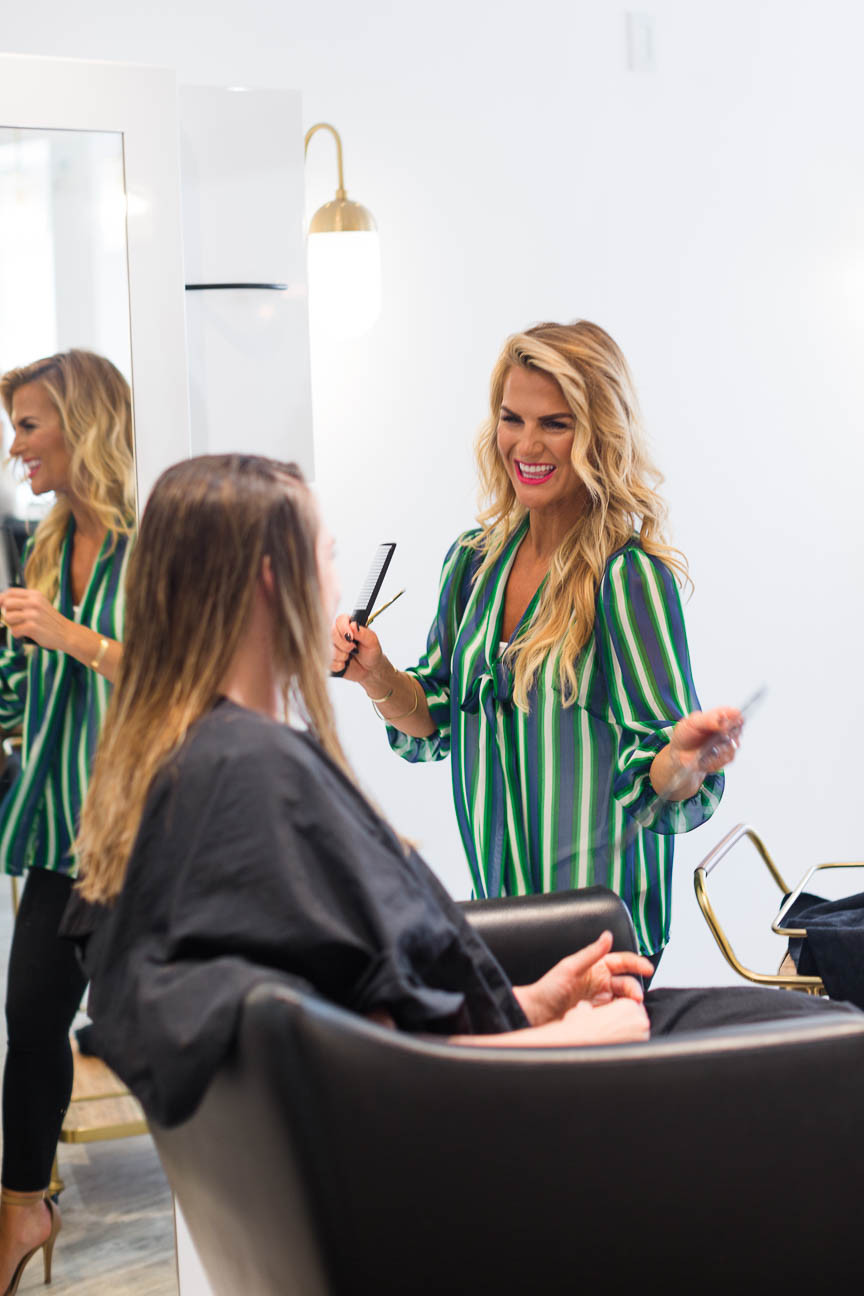 Jessica, owner, laughs with client while doing her hair