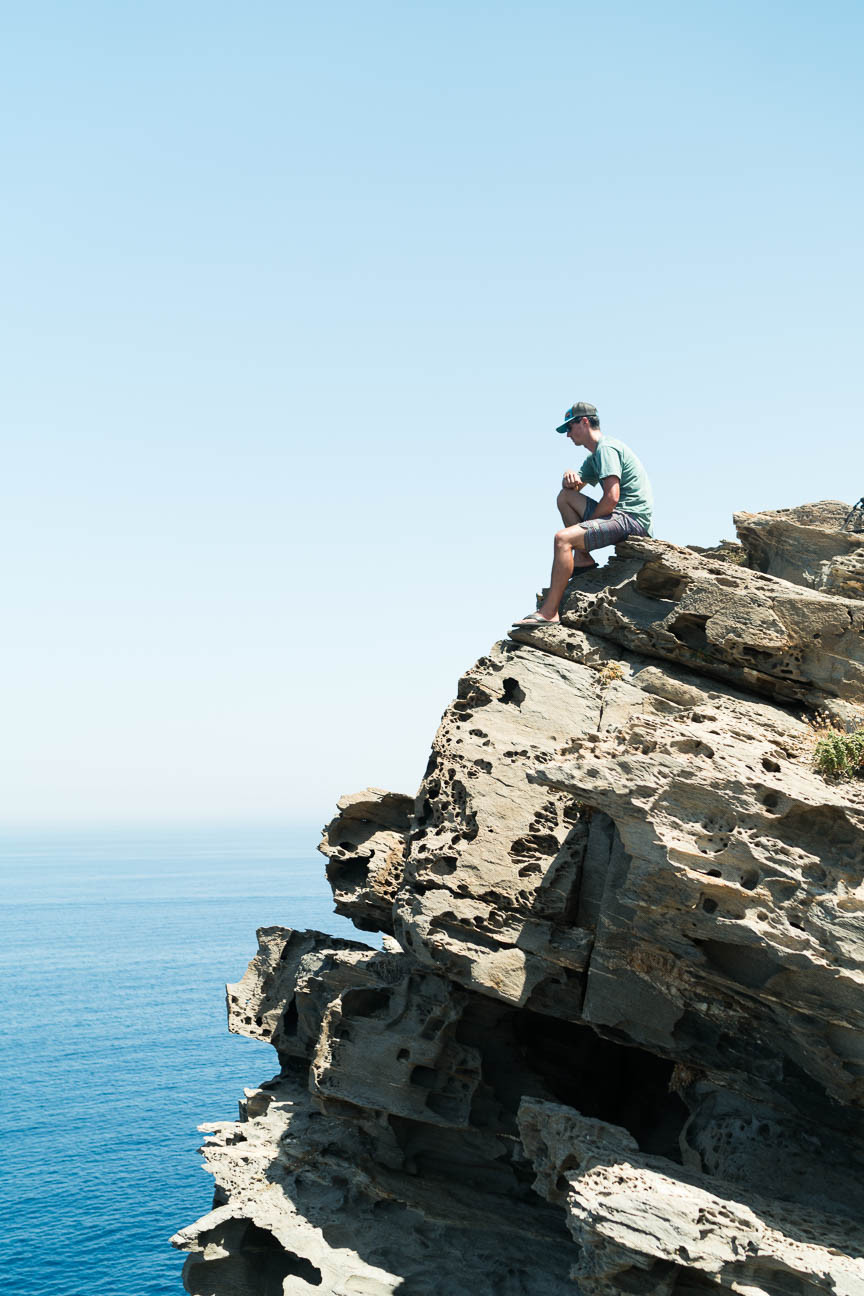 hiker sits on a rock clip overlooking the Agean Sea