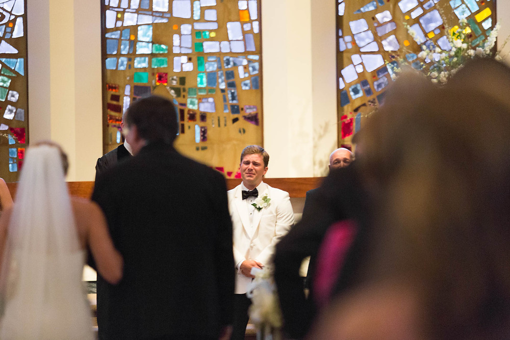 groom cries as he sees his bride walking down the aisle during a church ceremony