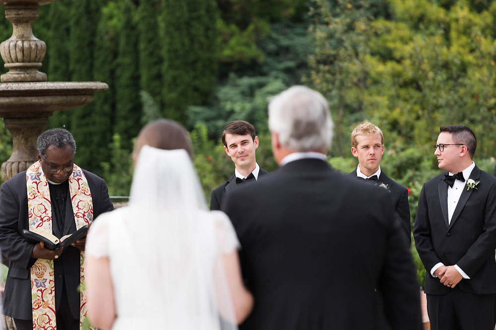 groom looks at bride as her father walks her down the aisle