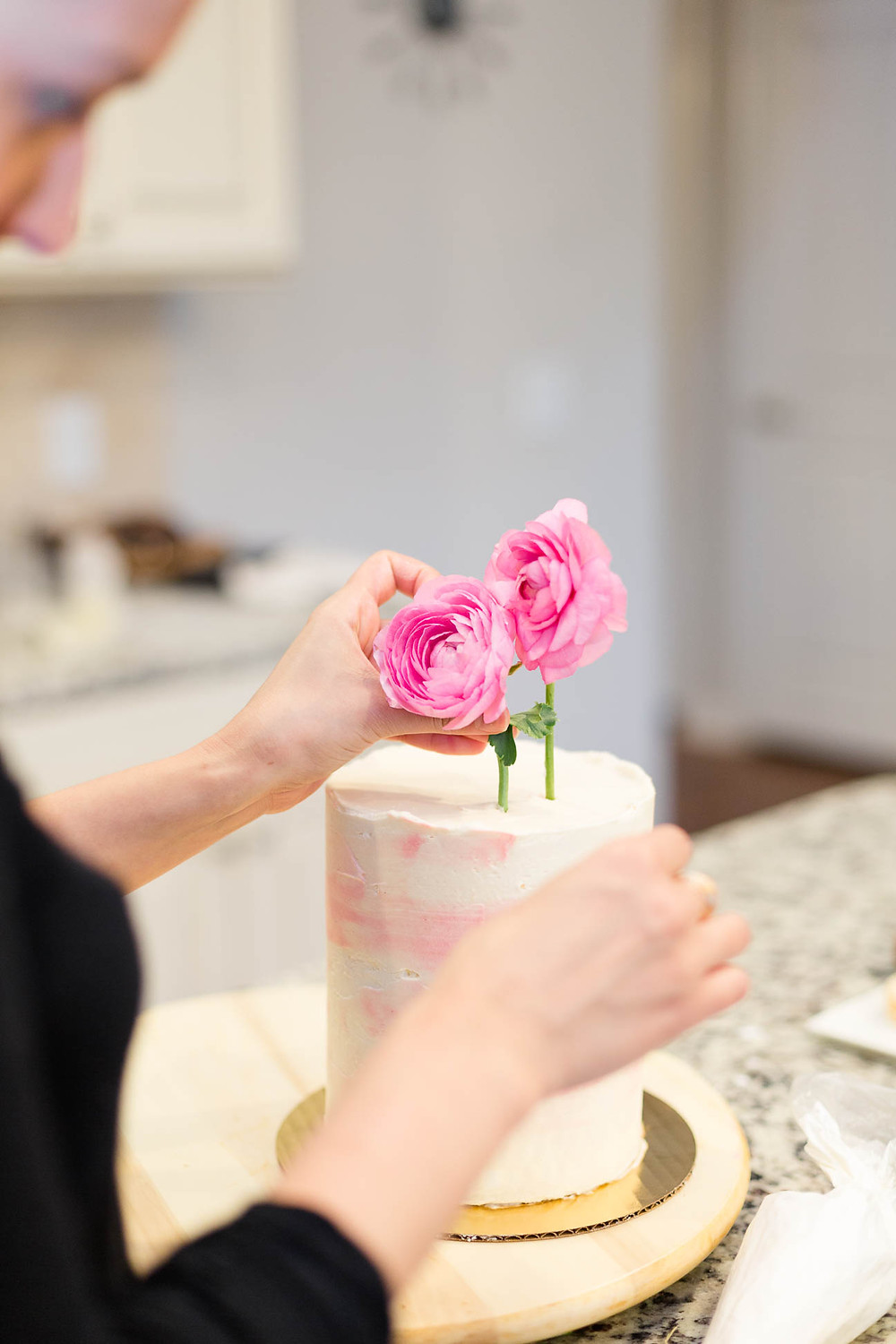 pink florals used to decorate a mini wedding cake with watercolor icing