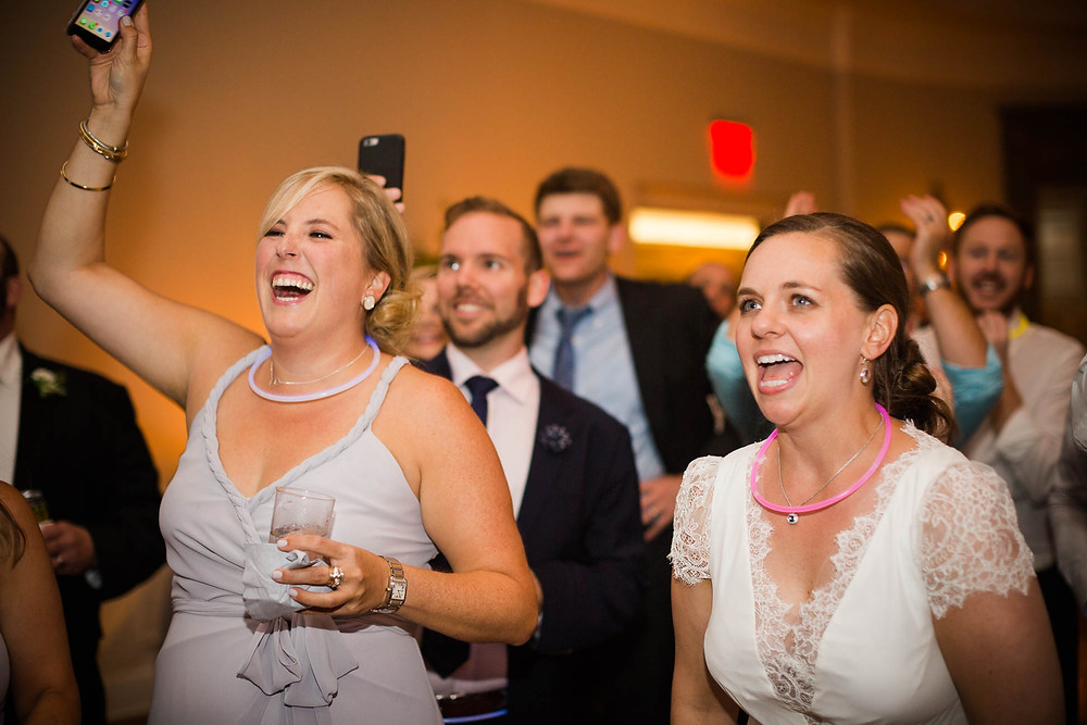 bride cheers for her husband as he sings on stage