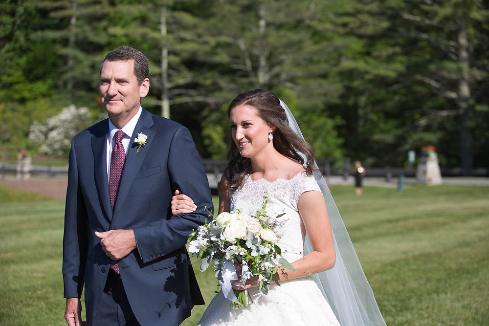 bride walks down the aisle with her father at mountain wedding