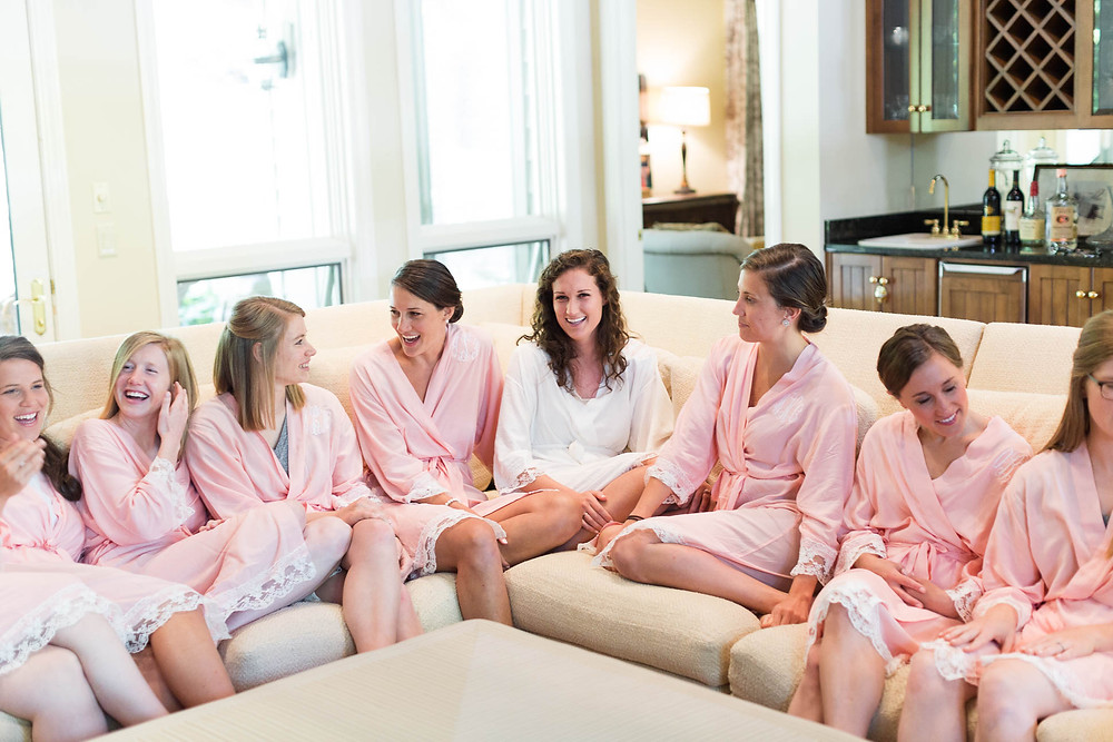 bridesmaids sit with bride in matching pink monogrammed robes