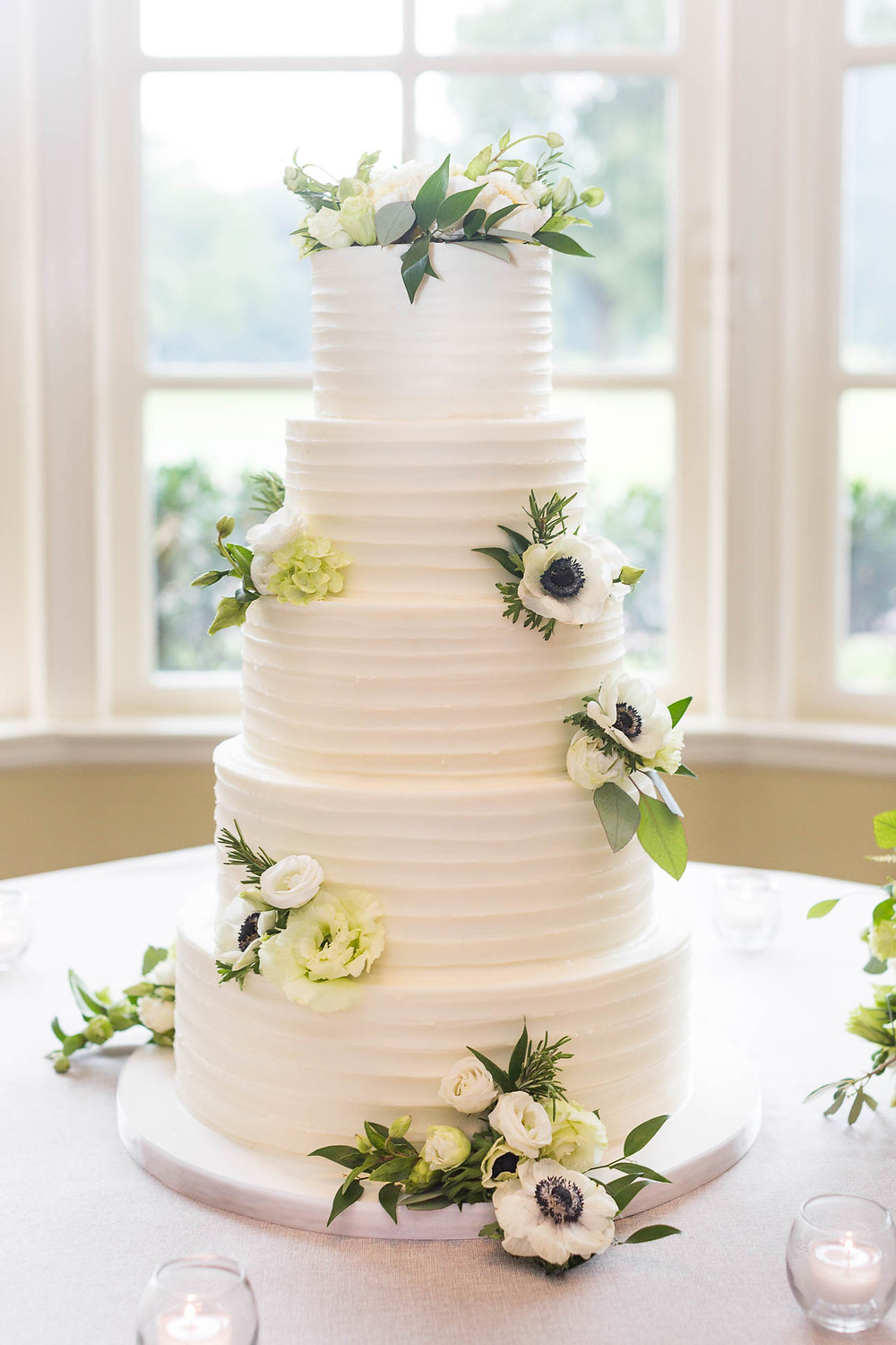 tall white wedding cake with flowers