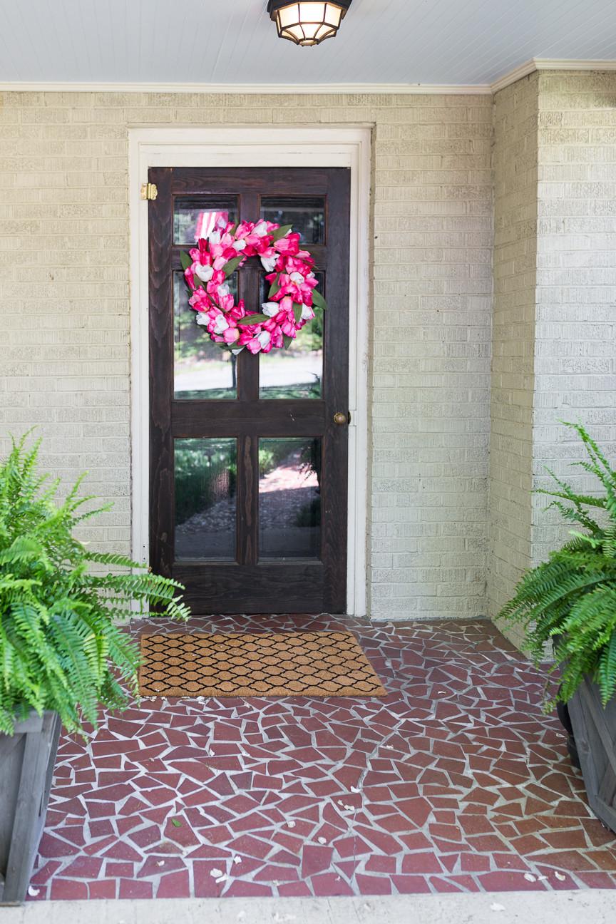 tulip wreath DIY hangs on a front door