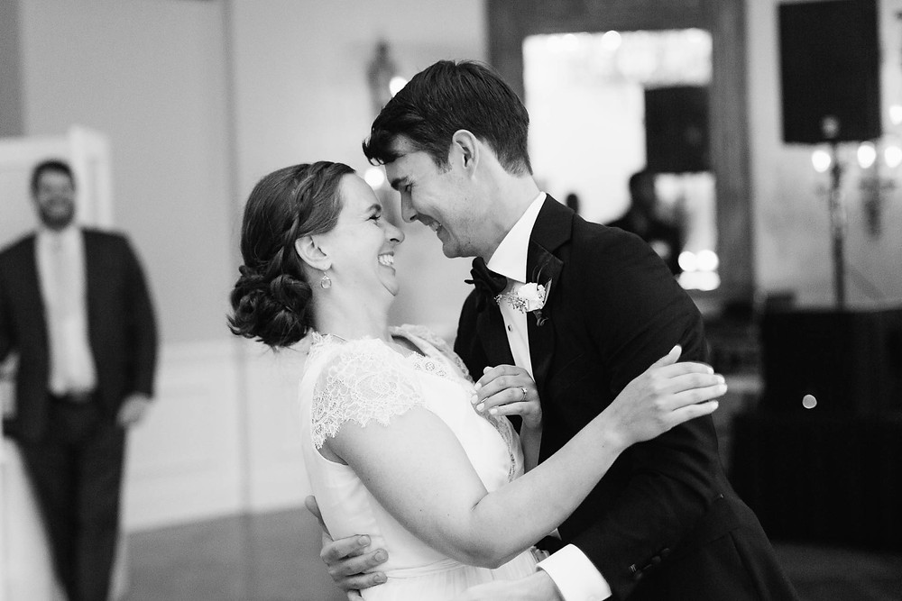couple smiles during their first dance as newlyweds
