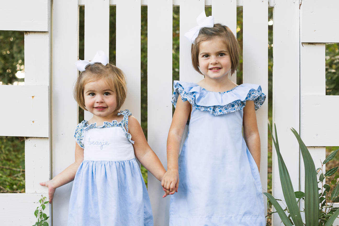 sisters standing in front of fence
