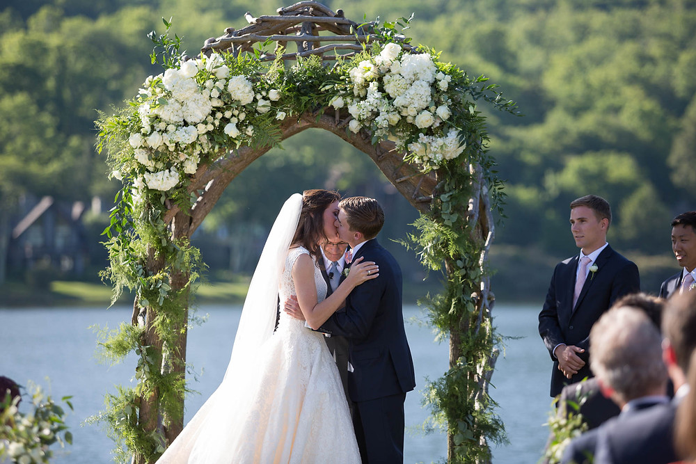 bride and groom's first kiss at their outdoor ceremony