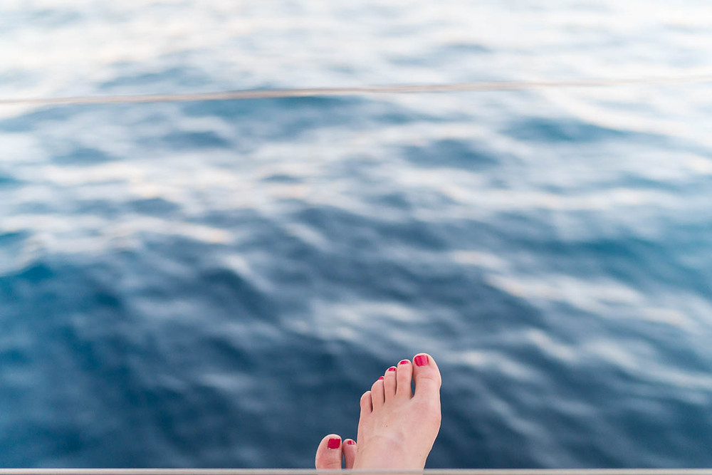 feet over the blue water of the Agean Sea