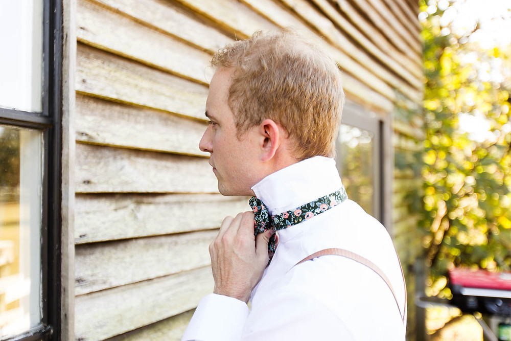 groom ties his bowtie